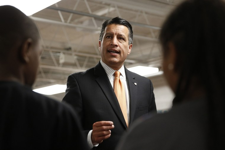 Nevada Governor Brian Sandoval holds a signing ceremony for Senate Bill 432, which allocates millions of dollars for low performing schools, June 3, 2015, in Las Vegas. (Photo by John Locher/AP)