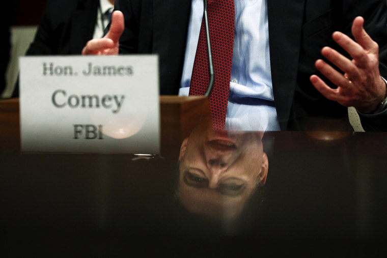 """FBI Director James Comey is seen in a reflection as he testifies in a House Appropriations hearing on """"World Wide Threats"""" on Capitol Hill in Washington, Feb. 25, 2016. (Photo by Kevin Lamarque/Reuters)"""