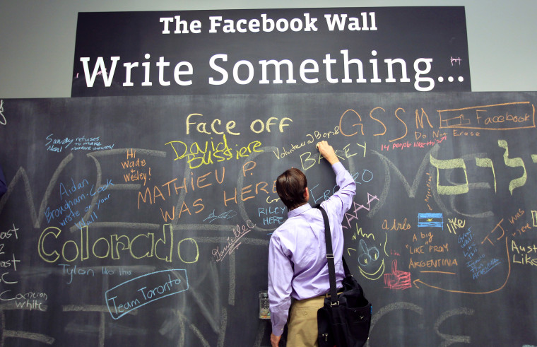 An employee writes a note on the message board at the new headquarters of Facebook in Menlo Park, Calif., Jan. 11, 2012. (Photo by Robert Galbraith/Reuters)