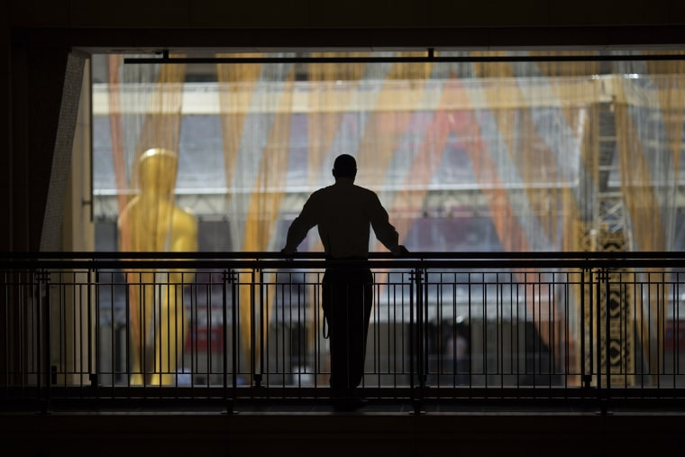 A security guard watches over operations near the primary Oscar statue as preparations are made for the 88th Annual Academy Awards at Hollywood & Highland Center on Feb. 24, 2016 in Hollywood, Calif. (Photo by David McNew/Getty)