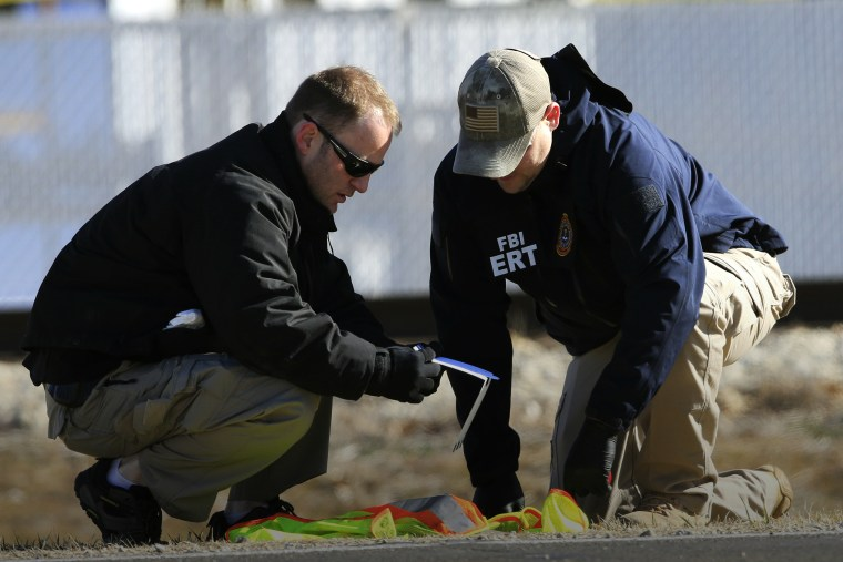 FBI agents look at evidence along Hesston Road outside Excel Industries in Hesston, Kan., Feb. 26, 2016. (Photo by Orlin Wagner/AP)