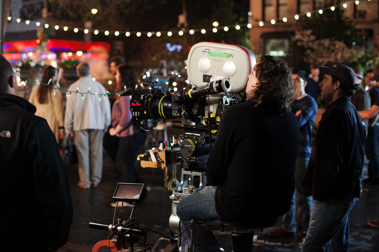 A camera operator prepares with his team and extras to film on location at Union Square, New York City, April 16, 2013. (Photo by Daniel Leal-Olivas/Corbis)