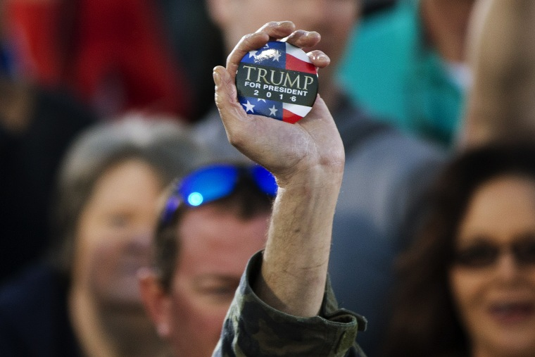 A man holds up a campaign button for Republican presidential candidate Donald Trump during a rally, Feb. 28, 2016, in Madison, Ala. (Photo by John Bazemore/AP)
