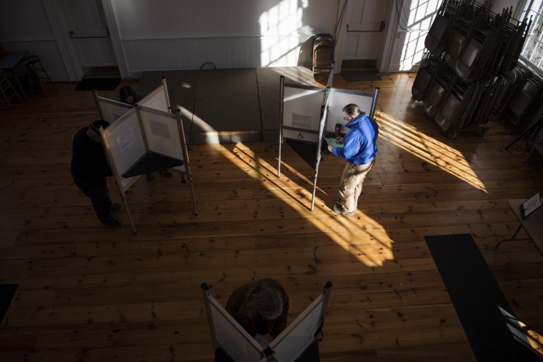 Voters cast their ballots in a polling station at the Ripton Town Clerk's office in Ripton, Vt.