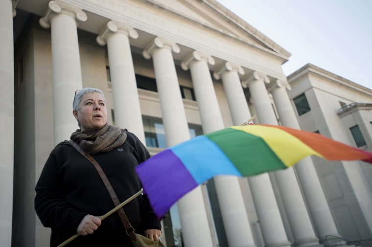 Minoo Vafai holds a rainbow flag during a rally against Alabama Chief Justice Roy Moore, Jan. 12, 2016, outside the Alabama Supreme Court building in Montgomery, Ala. (Photo by Albert Cesare/The Montgomery Advertiser/AP)