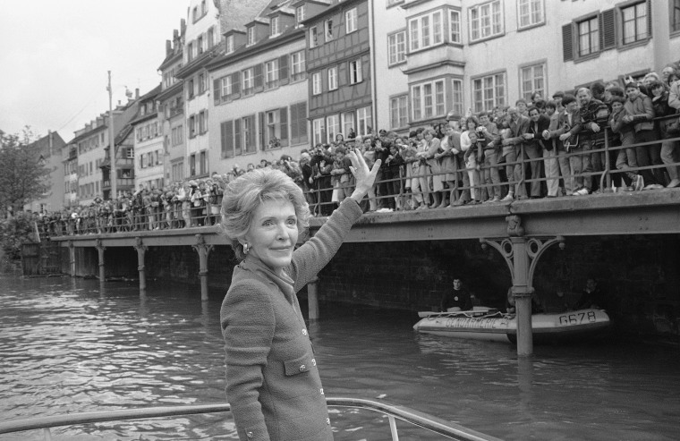 First Lady Nancy Reagan turns around and waves to a crowd alongside the river Ill where she was invited for a boat ride in this picturesque quarter, May 8, 1985, Strasbourg, France. (Anonymous/AP)