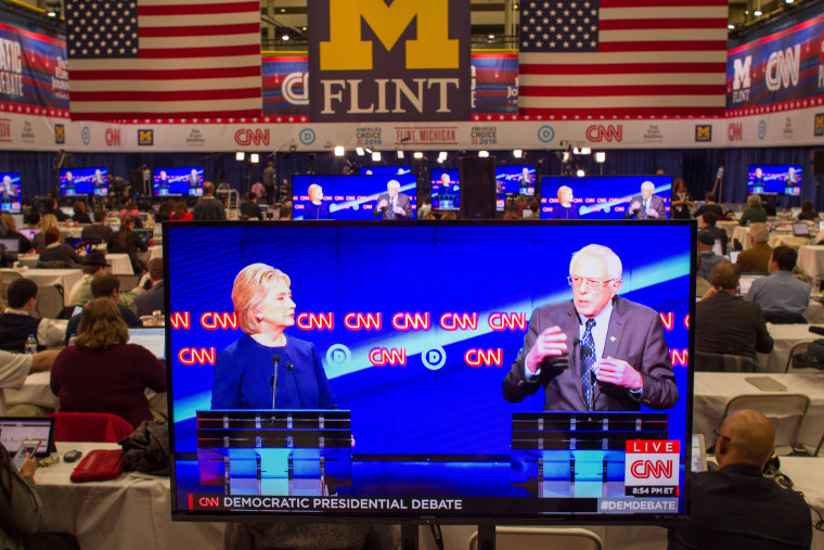 Journalists watch Democratic presidential candidates Hillary Clinton and Bernie Sanders debate on televisions in the media room at the University of Michigan in Flint, Mich. on March 6, 2016. (Photo by Geoff Robins/AFP/Getty)