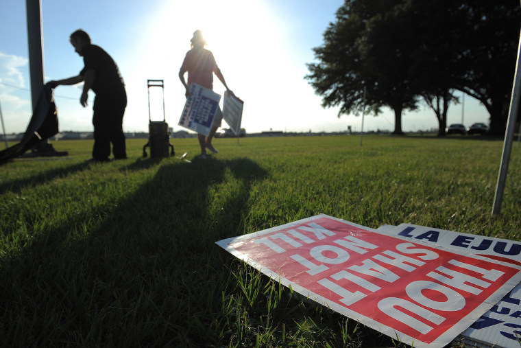 People opposed to the death penalty pick up signs as they gathered to demonstrate against the execution of John Ruthell Henry near the Florida State Prison on June 18, 2014 in Raiford, FL. (Photo by Matt McClain/The Washington Post/Getty)