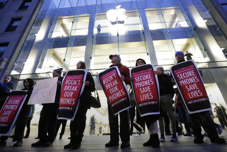 Protesters carry placards outside an Apple store in Boston, Feb. 23, 2016. (Photo by Steven Senne/AP)