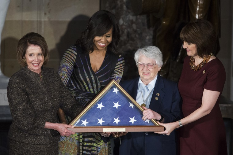 House Minority Leader Nancy Pelosi (D-CA) and First Lady Michelle Obama present an American flag to retired Air Force Brigadier Gen. Wilma Vaught on Capitol Hill, March 2, 2016 in Washington, DC. (Photo by Drew Angerer/Getty)