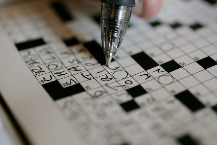 A puzzle fan works on the New York Times crossword puzzle. (Photo by Carolyn Kaster/AP)