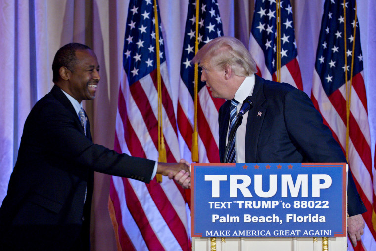 Donald Trump shakes hands with Ben Carson, retired neurosurgeon and former 2016 Republican presidential candidate, during a news conference at the Mar-A-Lago Club in Palm Beach, Fl., March 11, 2016. (Photo by Andrew Harrer/Bloomberg/Getty)