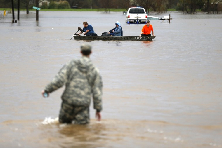 A Louisiana National Guardsman wades through water as residents are evacuated by boat through rising floodwaters in Bossier Parish, La., March 10, 2016. (Photo by Gerald Herbert/AP)