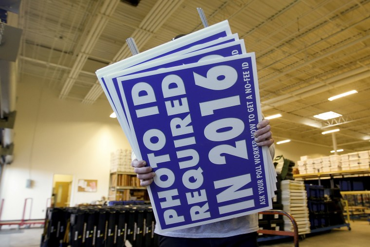 A worker carries a sign that will be displayed at a polling place that will inform voters of the new voter ID law that goes into effect in 2016 at the Mecklenburg County Board of Elections warehouse in Charlotte, N.C., Nov. 3, 2014.