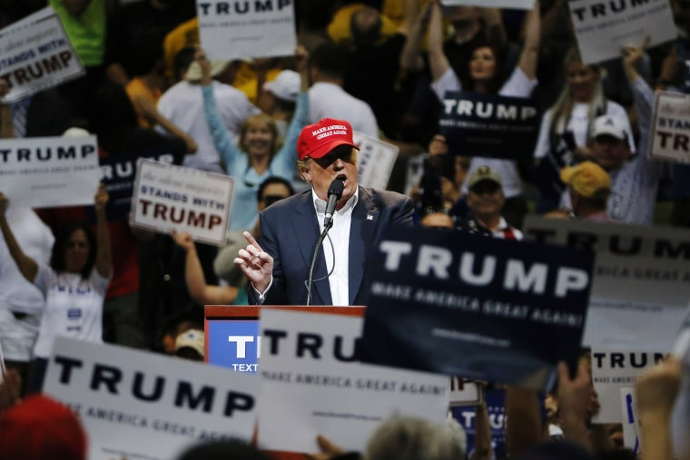 Among the waving of campaign signs, Republican presidential candidate Donald Trump speaks during a campaign rally, March 19, 2016, in Tucson, Ariz. (Photo by Ross D. Franklin/AP)