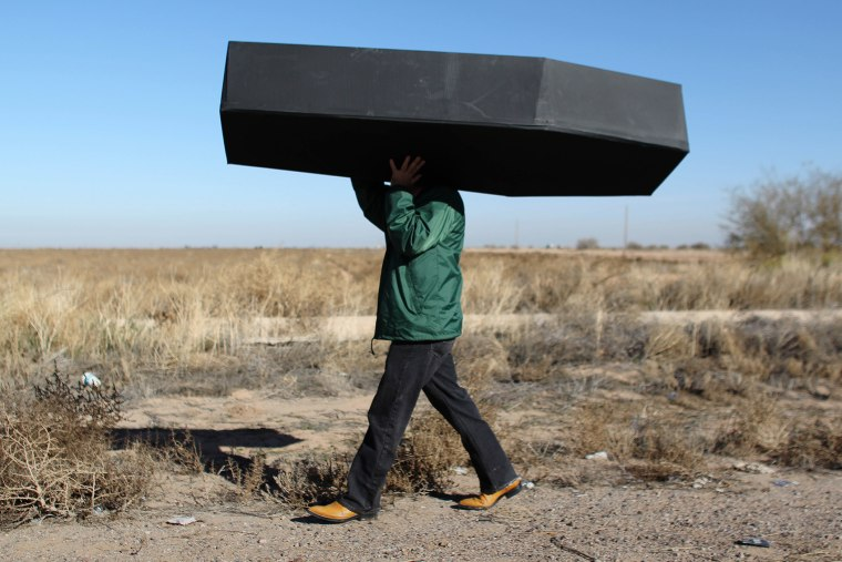 In this Jan. 20, 2016 file photo, a demonstrator carries a mock coffin, representing migrants who have died, outside the U.S. Immigration and Customs Enforcement detention center in Eloy, Ariz. (Photo by Ricardo Arduengo/AP)