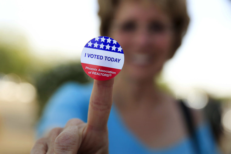 Deborah Kelly, who waited in line 45 minutes to vote in the presidential primary election, shows her voting sticker outside a polling site in Glendale, Ariz., March 22, 2016. (Photo by Nancy Wiechec/Reuters)