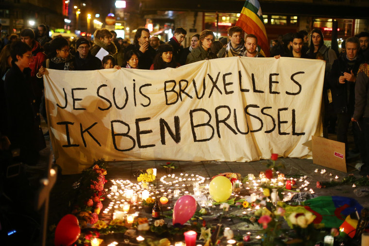 People hold up a banner as a mark of solidarity at the Place de la Bourse following today's attacks on March 22, 2016 in Brussels, Belgium. (Photo by Carl Court/Getty)