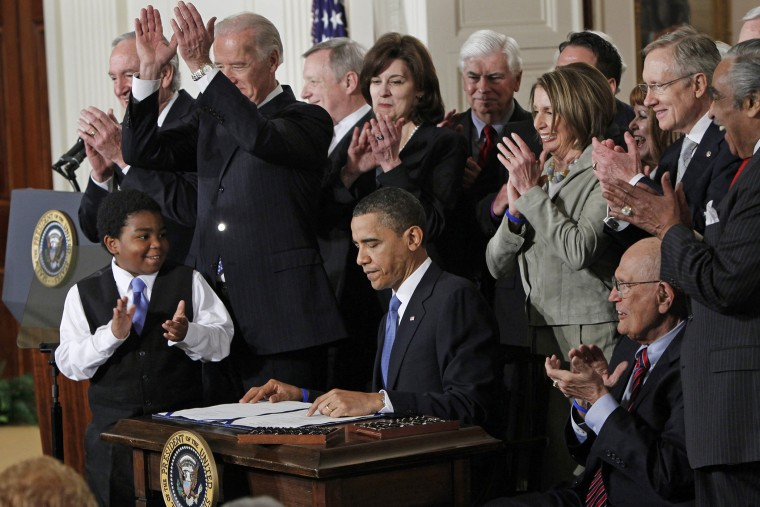 In this March 23, 2010, file photo, President Barack Obama is applauded after signing the Affordable Care Act into law in the East Room of the White House in Washington. (Photo by Charles Dharapak/AP)