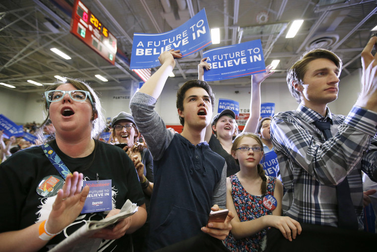 Supporters wave signs as Democratic presidential candidate Bernie Sanders speaks during a campaign rally at West High School on March 21, 2016 in Salt Lake City, Utah. (Photo by George Frey/Getty)