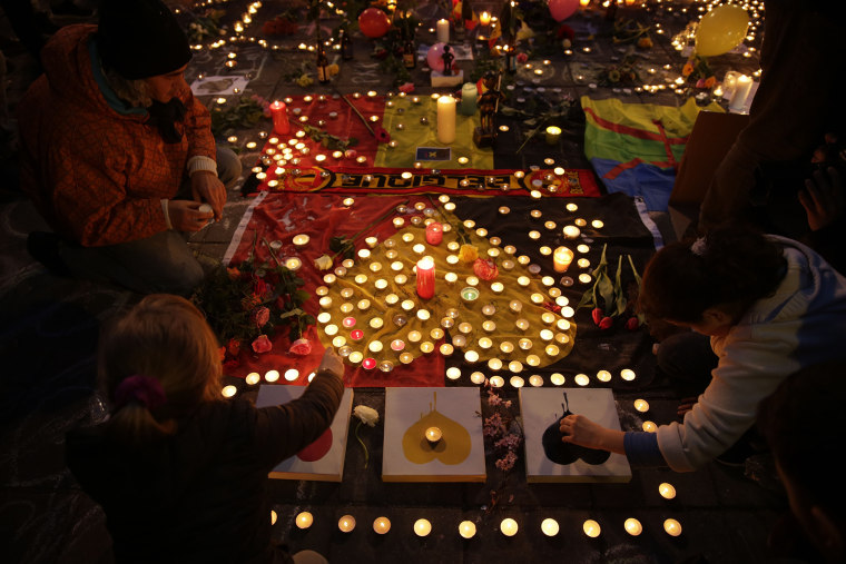 People light candles in tribute to victims at a makeshift memorial in front of the stock exchange at the Place de la Bourse (Beursplein) in Brussels on March 22, 2016. (Photo by Kenzo Tribouillard/AFP/Getty)