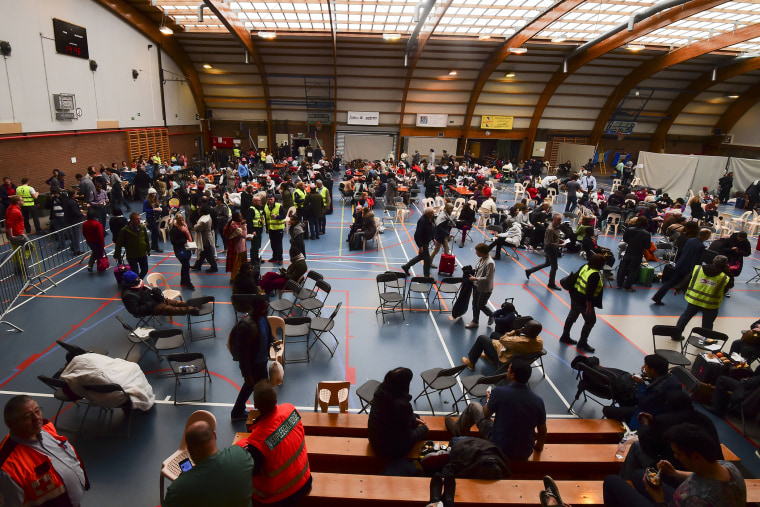 Travellers who were evacuated from Brussels airport take shelter at a sports complex in Zaventem following blasts on March 22, 2016. (Photo by John Thys/AFP/Getty)