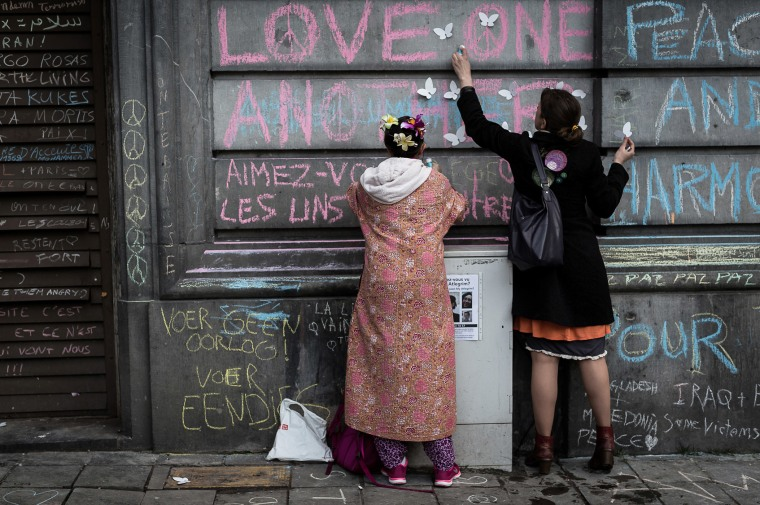 Two children write on a wall at a memorial for victims of attacks in Brussels on March 23, 2016. (Photo by Valentin Bianchi/AP)
