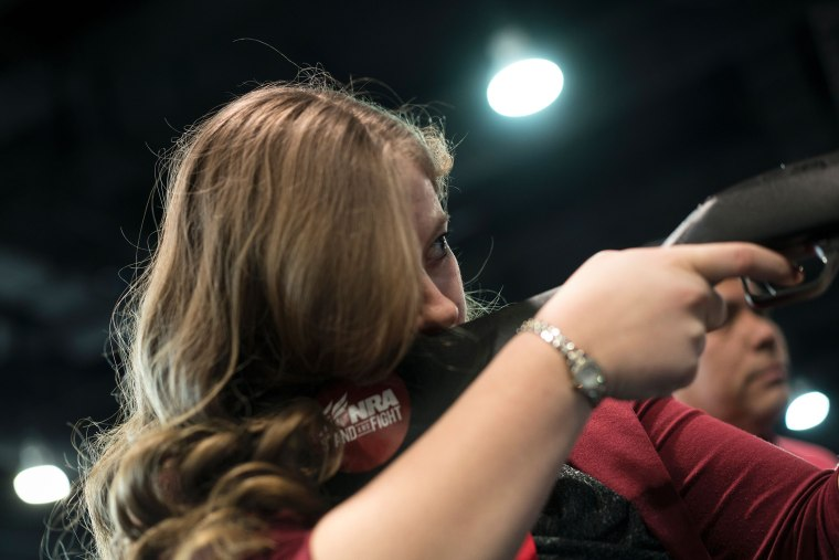 A woman uses a rifle in a laser shooting simulation by the NRA during the American Conservative Union Conservative Political Action Conference 2016, March 4, 2016, in Oxon Hill, Md. (Photo by Brendan Smialowski/AFP/Getty)