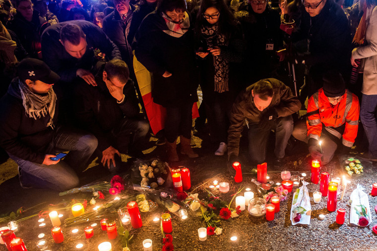 Brussels airport workers and their relatives place candles at a makeshift memorial as they pay tribute to the victims of Brussels triple attacks near the airport in Zaventem on March 23, 2016. (Photo by Philippe Huguen/AFP/Getty)