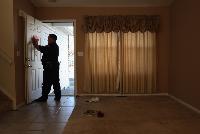 "A sheriff's deputy tapes a ""no trespass order"" on the front door of a home, Feb. 18, 2009 in Longmont, Colo.  (Photo by John Moore/Getty)"