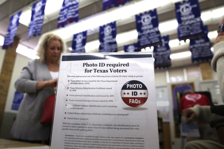 A sign tells voters of voter ID requirements before participating in the primary election at Sherrod Elementary school in Arlington, Texas, March 1, 2016. (Photo by LM Otero/AP)