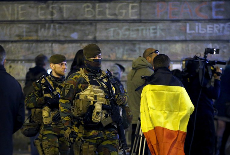 Belgian soldiers patrol as people pay tribute to the victims of Tuesday's bomb attacks at the Place de la Bourse in Brussels, Belgium, March 26, 2016. (Photo by Francois Lenoir/Reuters)