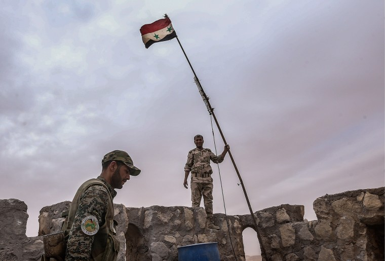 Syrian government army soldiers put a flag on top of Fakhr al-Din al-Maani Citadel, a UNESCO world heritage site. The Syrian Government's army has won control of the heritage site from ISIS militants. (Photo by Valery Sharifulin/TASS/Getty)