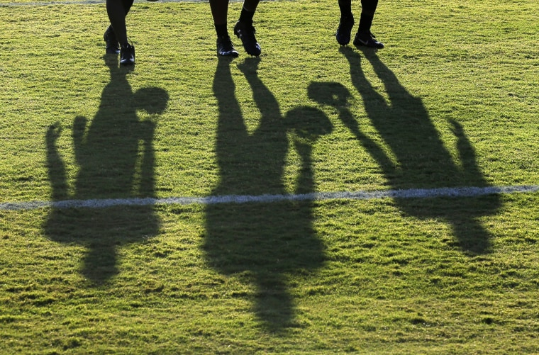 Baltimore Ravens wide receivers cast shadows as they walk off the field after NFL football training camp, Aug. 8, 2015, in Owings Mills, Md.