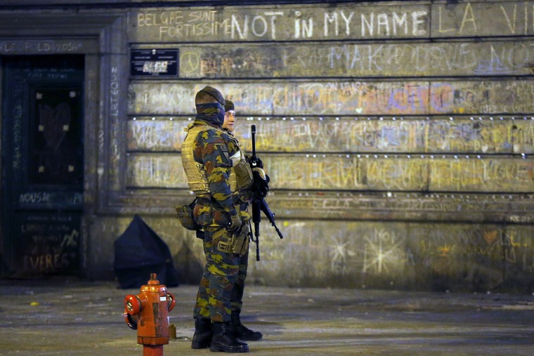 Belgian soldiers patrol, as people pay tribute to the victims of Tuesday's bomb attacks, at the Place de la Bourse in Brussels, Belgium, March 26, 2016. (Photo by Francois Lenoir/Reuters)