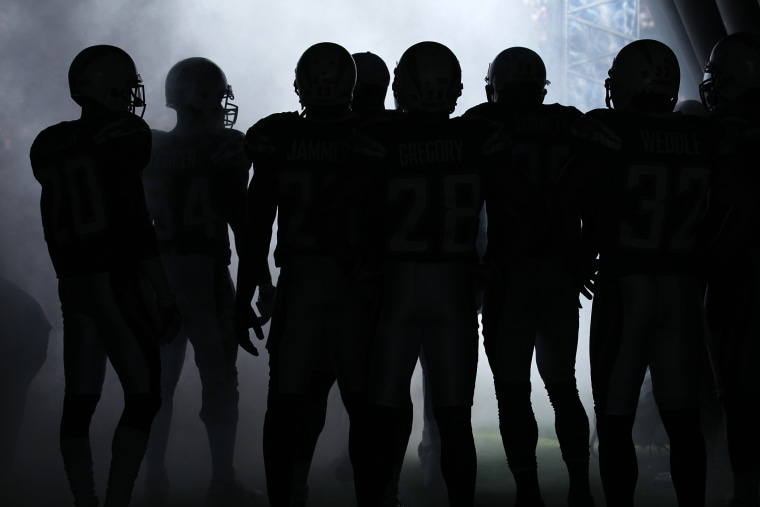 NFL players wait to be introduced to the crowd before playing in a game. (Photo by Mike Blake/Reuters)