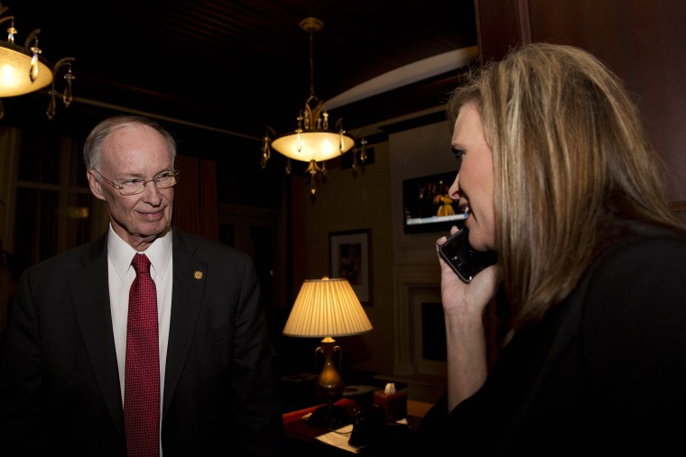In this Tuesday, Nov. 4, 2014 file photo, Republican Gov. Robert Bentley listens to a phone call as Rebekah Mason, right, announces his win for Alabama governor, in Montgomery, Ala. (Photo by Brynn Anderson/AP)