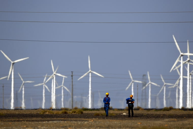 Workers walk near wind turbines for generating electricity, at a wind farm in Guazhou, 950km (590 miles) northwest of Lanzhou, Gansu Province, Sep. 15, 2013. (Photo by Carlos Barria/Reuters)