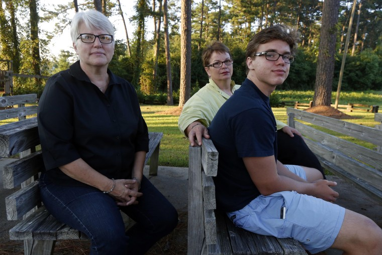 Hudson Garner, 15, right, sits outside with his mothers Kathryn Garner, and Susan Hrostowski, left, in Collins, Miss., Aug. 12, 2015. (Photo by Rogelio V. Solis/AP