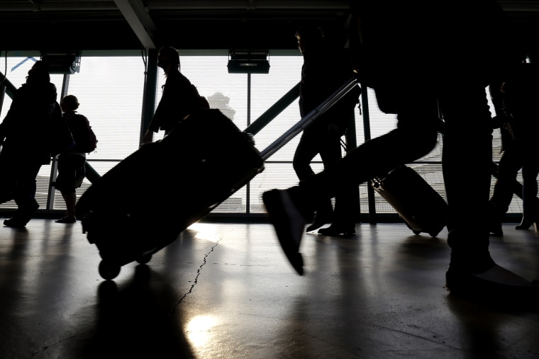 Travelers walk through O'Hare International airport in Chicago, Ill. (Photo by Nam Y. Huh/AP)