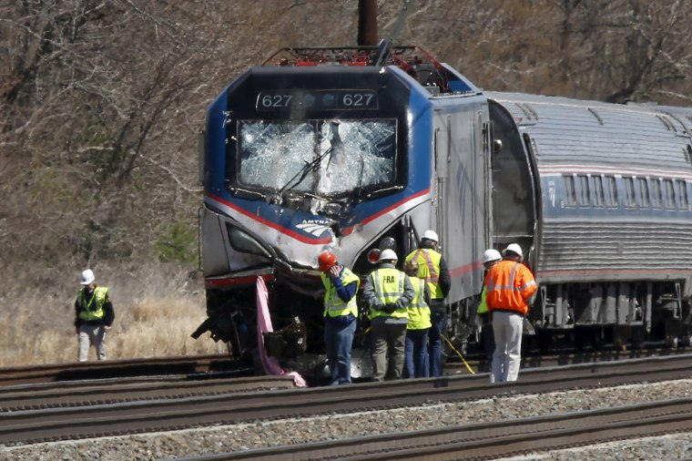 Emergency personnel examine the scene after an Amtrak passenger train struck a backhoe, killing two people, in Chester, Penn., April 3, 2016. (Photo by Dominick Reuter/Reuters)