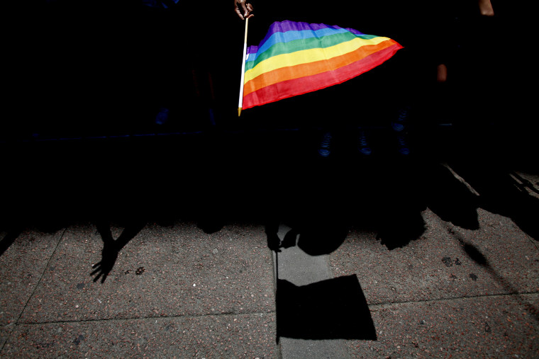 A parade goer waves a pride flag. (Photo by Sarah Rice/Getty)