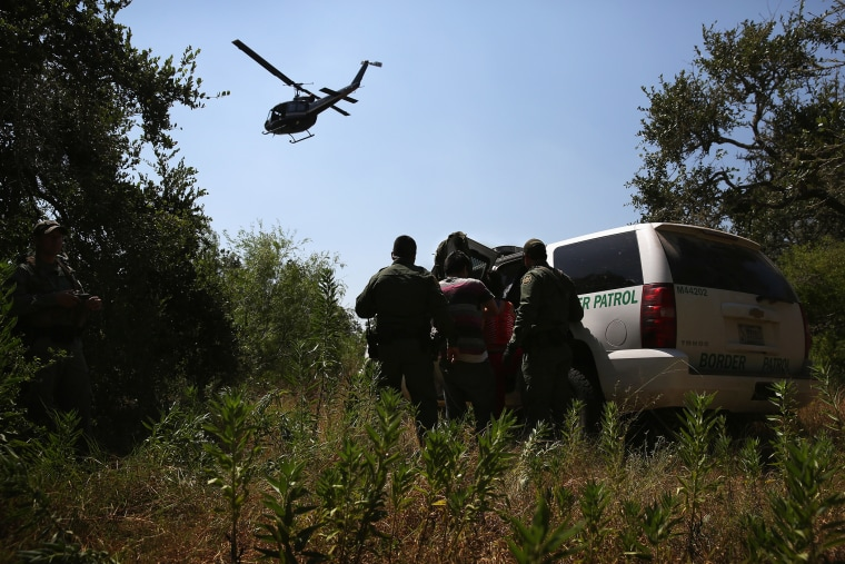 U.S. Border Patrol agents detain undocumented immigrants with the help of helicopter support from the U.S. Office of Air and Marine north of the U.S.-Mexico border on Aug. 6, 2015 near Falfurrias, Texas. (Photo by John Moore/Getty)