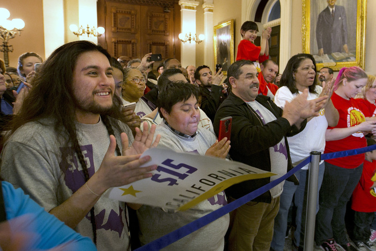 Supporters of a bill to raise California's minimum wage, celebrate outside the state Senate Chamber after the measure was approved by the Senate, March 31, 2016, in Sacramento, Calif. (Photo by Rich Pedroncelli/AP)
