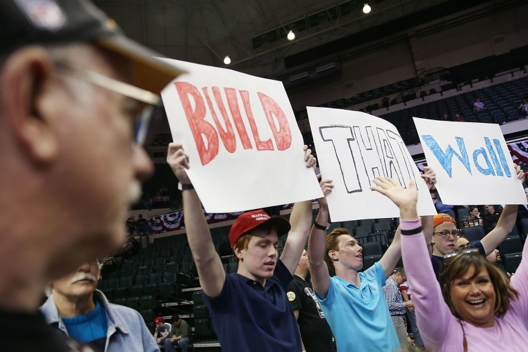 """People hold signs that read, """" Build that Wall"""", as they wait for the start of a campaign rally for Republican presidential candidate Donald Trump at the University of South Florida on Feb. 12, 2016 in Tampa, Fla. (Photo by Joe Raedle/Getty)"""