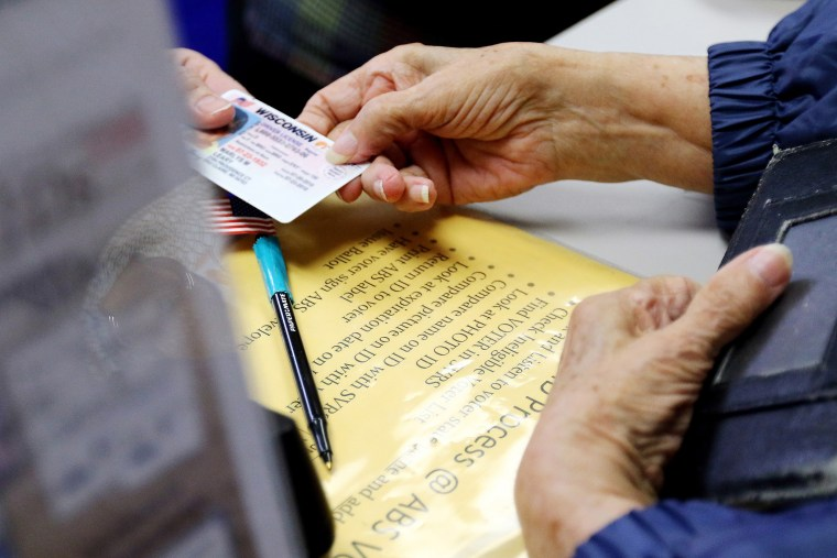 A voter in Eau Claire, Wis. hands her photo identification card to an election assistant on March 21, 2016, at the City of Eau Claire Elections Office. (Photo by Marisa Wojcik/The Eau Claire Leader-Telegram/AP)