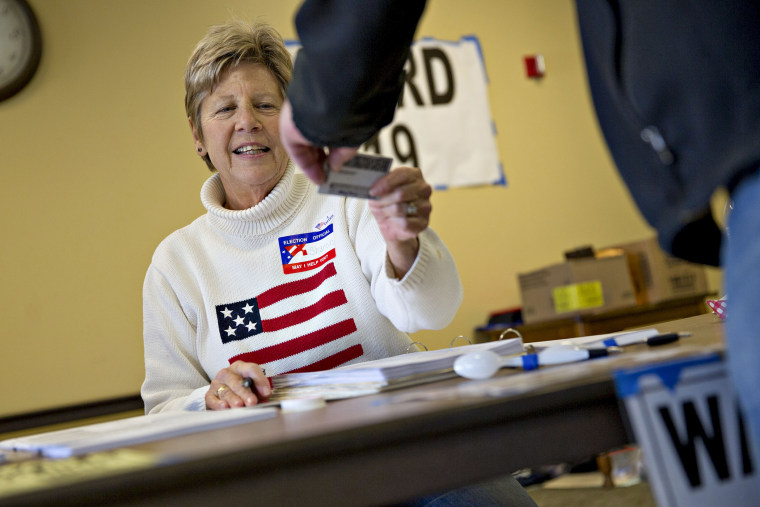 A poll worker checks the identification of a resident at polling location during the presidential primary vote in Waukesha, Wis., April 5, 2016. (Photo by Daniel Acker/Bloomberg/Getty)