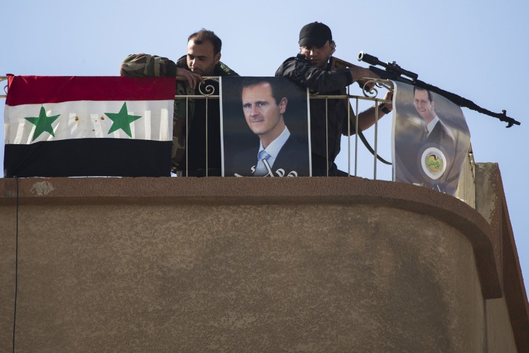 Syrian solders keep watch on a roof with portraits of Syrian President Bashar Assad in Al-Tall, a town of northern outskirts of Damascus, Syria, March 3, 2016. (Photo by Pavel Golovkin/AP)
