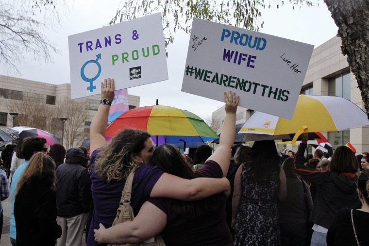 Two protesters hold up signs against passage of legislation in North Carolina, which limits the bathroom options for transgender people, during a rally in Charlotte, N.C., March 31, 2016. (Photo by Skip Foreman/AP)