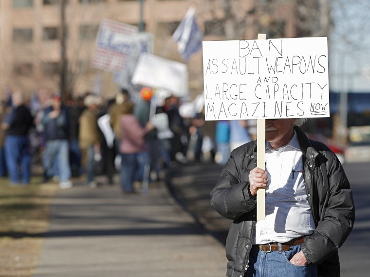 A lone anti-gun activist protests as Second Amendment demonstrators rally on Jan. 9, 2013 at the Colorado State Capitol in Denver, Colo. (Photo by Marc Piscotty/Getty)